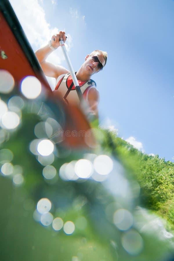 Κωπηλασία σε κανό νεαρών άνδρων στοκ φωτογραφία με δικαίωμα ελεύθερης χρήσης