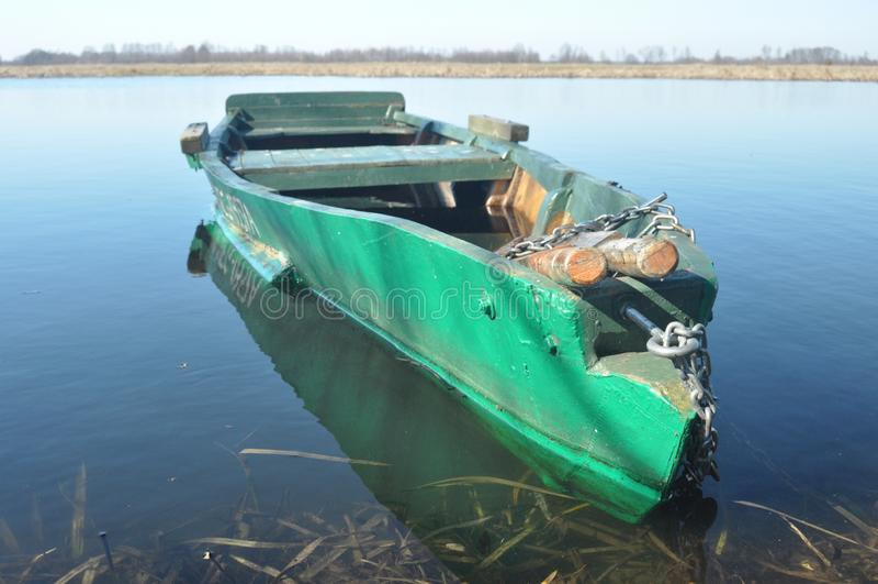 Κωπηλατώντας τη βάρκα που δένεται στην ακτή Άνοιξη στον ποταμό floating στοκ εικόνα