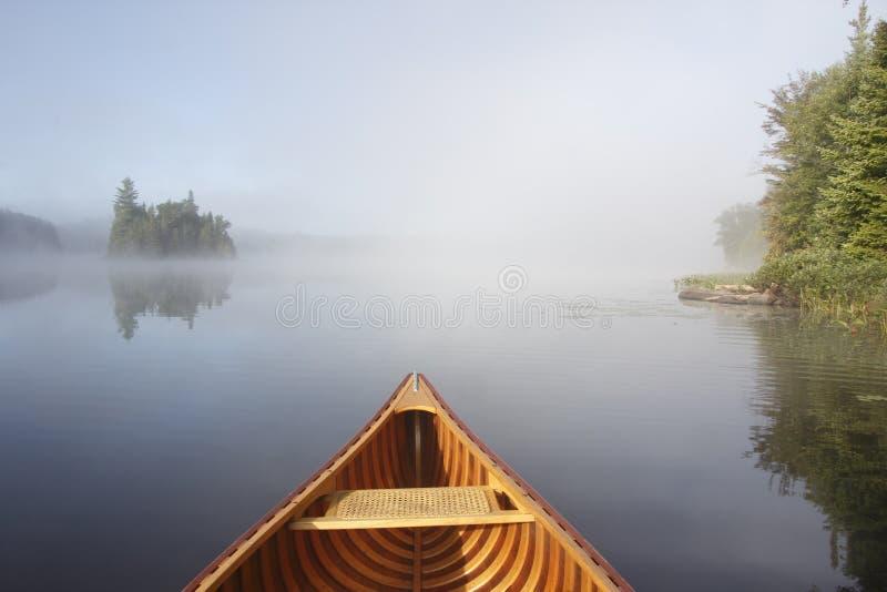 Κωπηλασία σε κανό σε μια ήρεμη λίμνη στοκ εικόνα