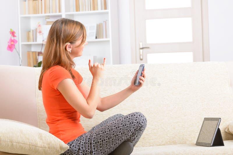 Κωφή γυναίκα που χρησιμοποιεί τη γλώσσα σημαδιών στο smartphone στοκ φωτογραφίες