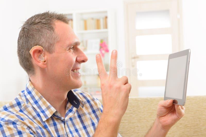 Κωφό άτομο που χρησιμοποιεί τη γλώσσα σημαδιών στην ταμπλέτα στοκ εικόνες