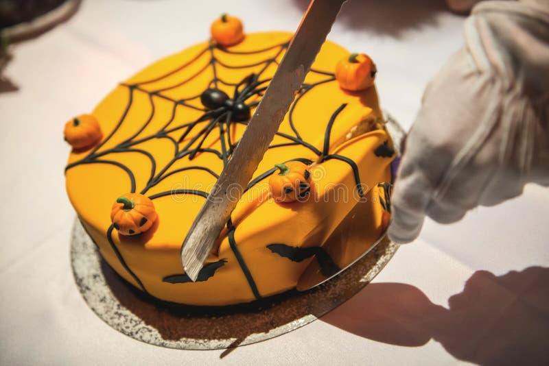 Κόβοντας το κέικ αποκριών που διακοσμείται με τις κολοκύθες, την αράχνη και τον Ιστό στοκ εικόνα με δικαίωμα ελεύθερης χρήσης