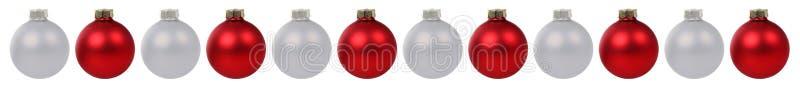 Κόκκινα ασημένια σύνορα μπιχλιμπιδιών σφαιρών Χριστουγέννων σε μια σειρά που απομονώνεται ελεύθερη απεικόνιση δικαιώματος