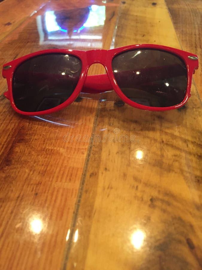 Κόκκινα γυαλιά ηλίου στον ξύλινο πίνακα στοκ φωτογραφία