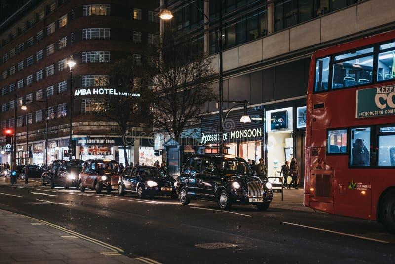 Κόκκινα διπλά λεωφορεία και taxis καταστρωμάτων στην οδό της Οξφόρδης, Λονδίνο, UK, το βράδυ στοκ εικόνες