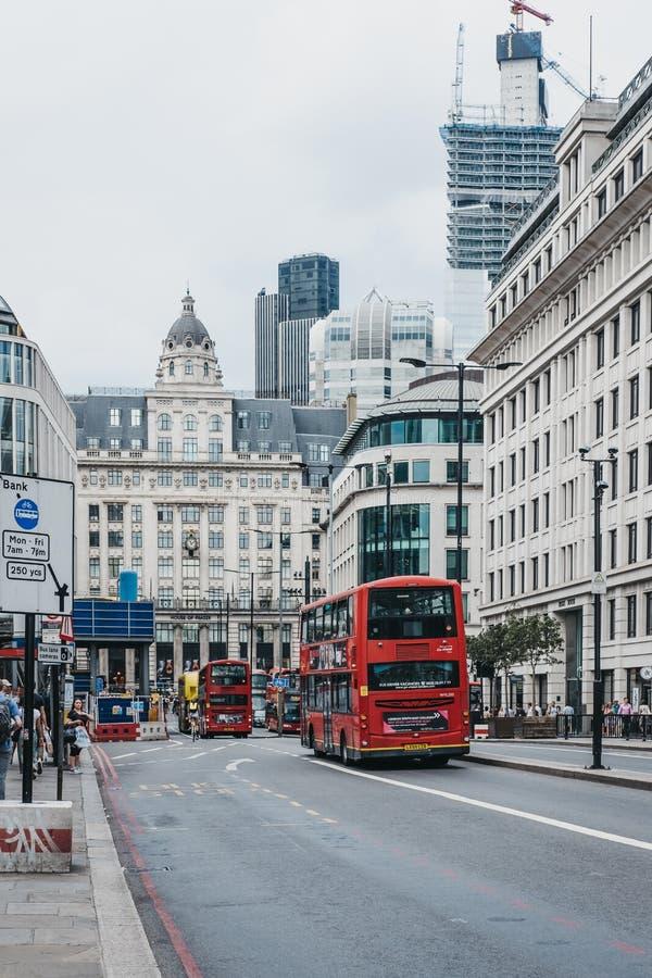 Κόκκινα διπλά λεωφορεία καταστρωμάτων στην οδό του William βασιλιάδων στην πόλη του Λονδίνου, Λονδίνο, UK στοκ εικόνες