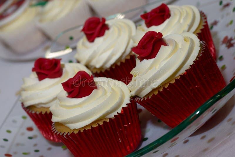Κόκκινα κέικ φλυτζανιών με τα τριαντάφυλλα στην κορυφή στοκ εικόνα με δικαίωμα ελεύθερης χρήσης