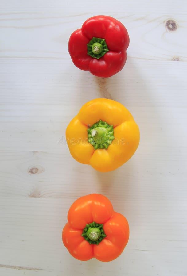 Κόκκινα, κίτρινα και πορτοκαλιά πιπέρια κουδουνιών που παρατάσσονται στο υπόβαθρο σανίδων r στοκ εικόνα