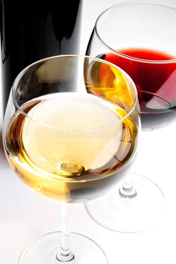 Κόκκινα και άσπρα γυαλιά κρασιού με το μαύρο μπουκάλι στοκ εικόνες