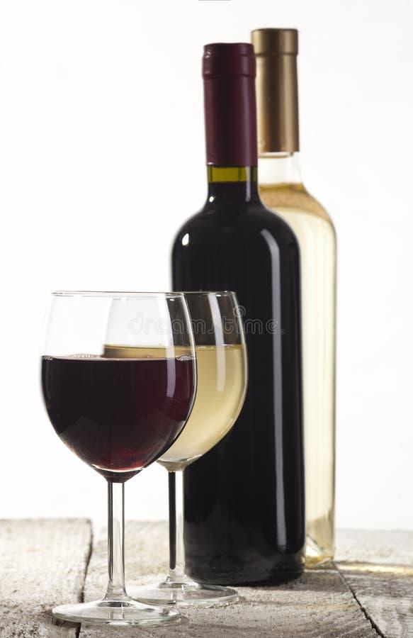 Κόκκινα και άσπρα μπουκάλια κρασιού με τα γυαλιά στοκ εικόνες με δικαίωμα ελεύθερης χρήσης