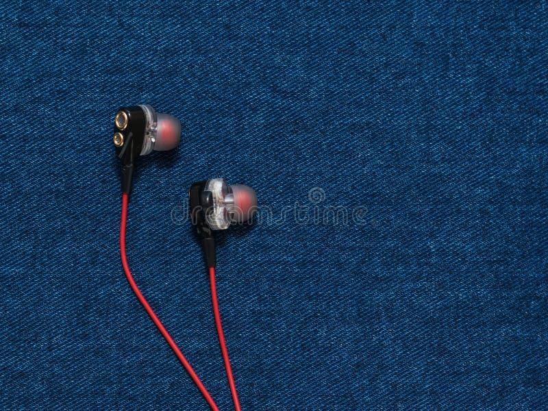 Κόκκινα και μαύρα ακουστικά σε ένα επίπεδο υπόβαθρο τζιν στοκ φωτογραφία με δικαίωμα ελεύθερης χρήσης