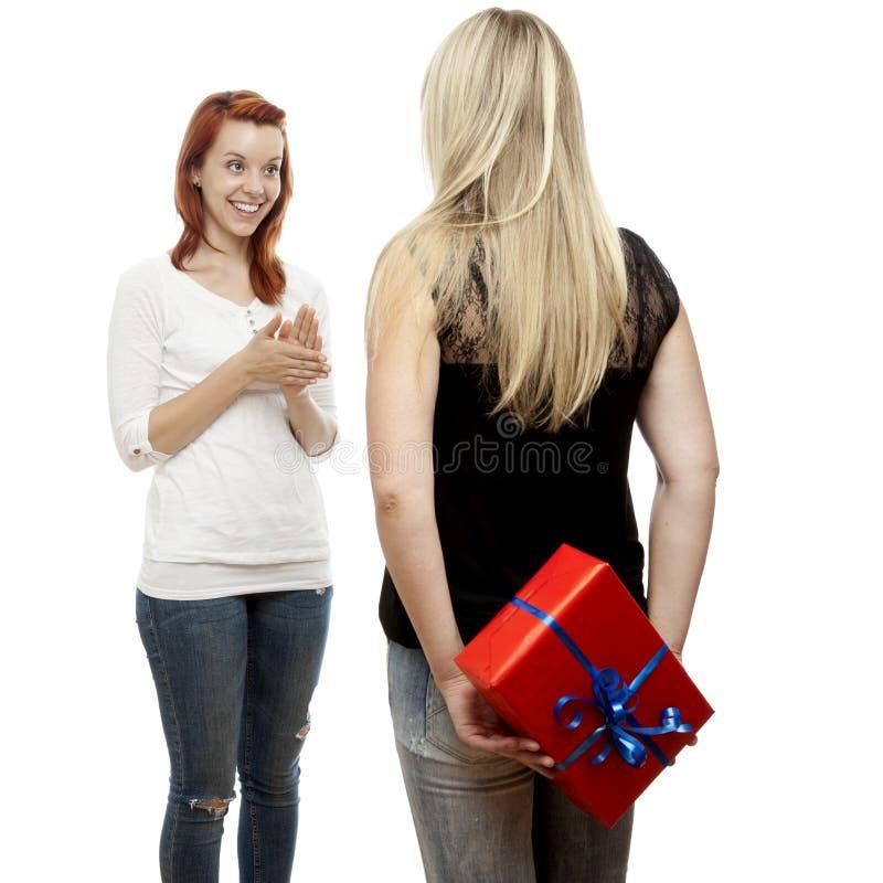 Κόκκινα και ξανθά μαλλιαρά κορίτσια με το δώρο πίσω από την πλάτη στοκ εικόνα με δικαίωμα ελεύθερης χρήσης
