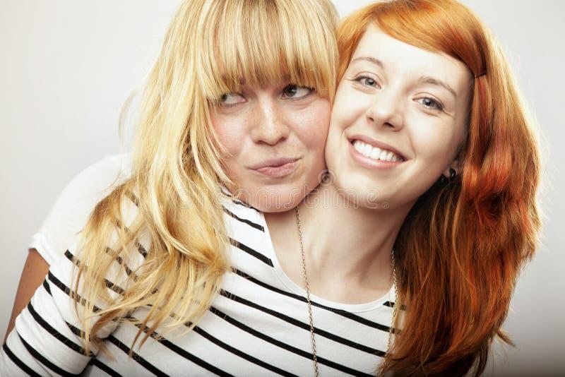 Κόκκινα και ξανθά μαλλιαρά γέλιο και αγκάλιασμα φίλων κοριτσιών στοκ φωτογραφίες