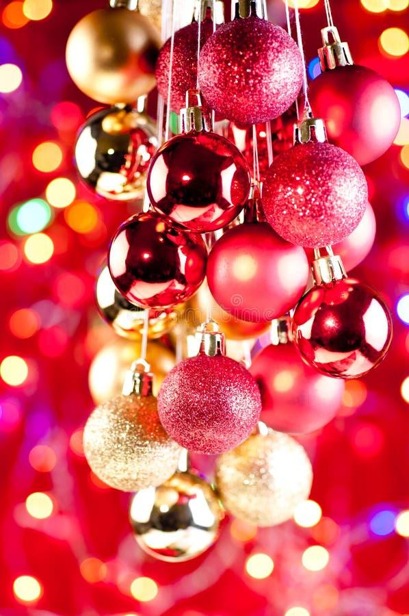 Κόκκινα και χρυσά κρεμώντας μπιχλιμπίδια Χριστουγέννων κοντά επάνω στοκ φωτογραφία