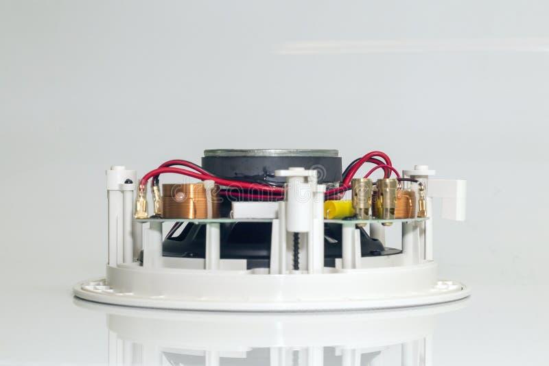 Κόκκινα καλώδια και χρυσοί συνδετήρες σε ένα άσπρο μεγάφωνο στοκ εικόνα