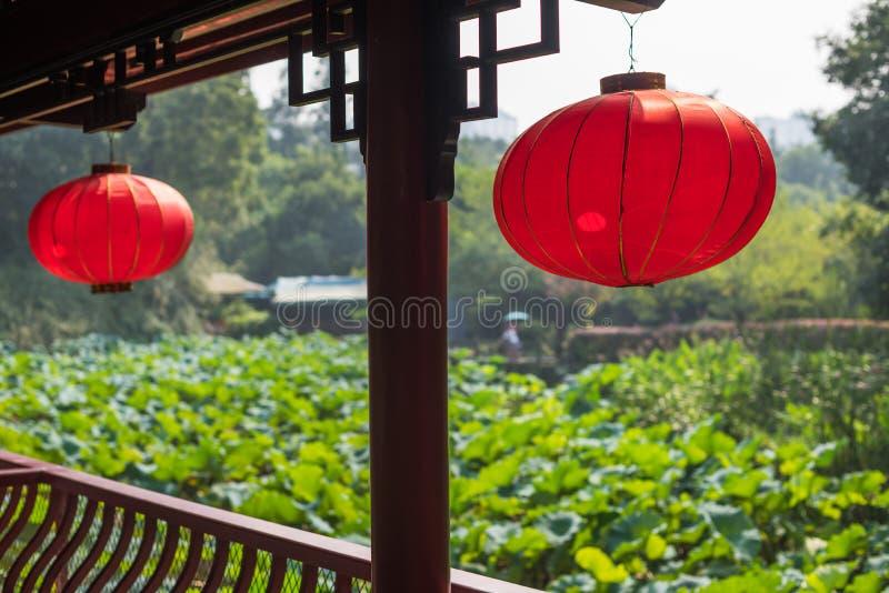 Κόκκινα κινεζικά φανάρια που κρεμούν με μια λίμνη των φύλλων λωτού στοκ εικόνες με δικαίωμα ελεύθερης χρήσης