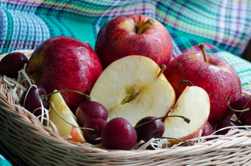 Κόκκινα μήλα και κεράσι σε μια πετσέτα στοκ εικόνα