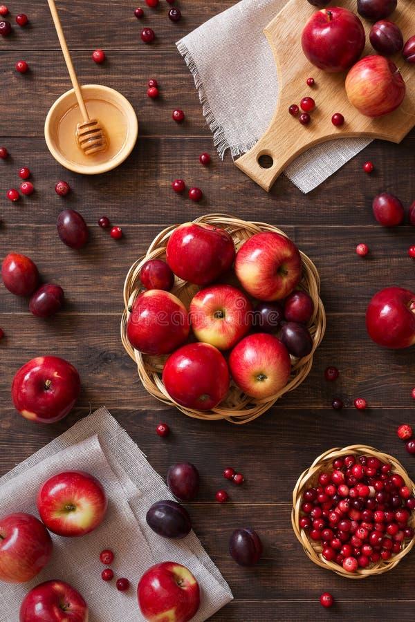 Κόκκινα μήλα με τα δαμάσκηνα και τα τα βακκίνια στοκ φωτογραφία