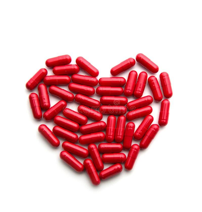 Κόκκινα μακριά χάπια σε μια μορφή καρδιών στοκ εικόνες με δικαίωμα ελεύθερης χρήσης