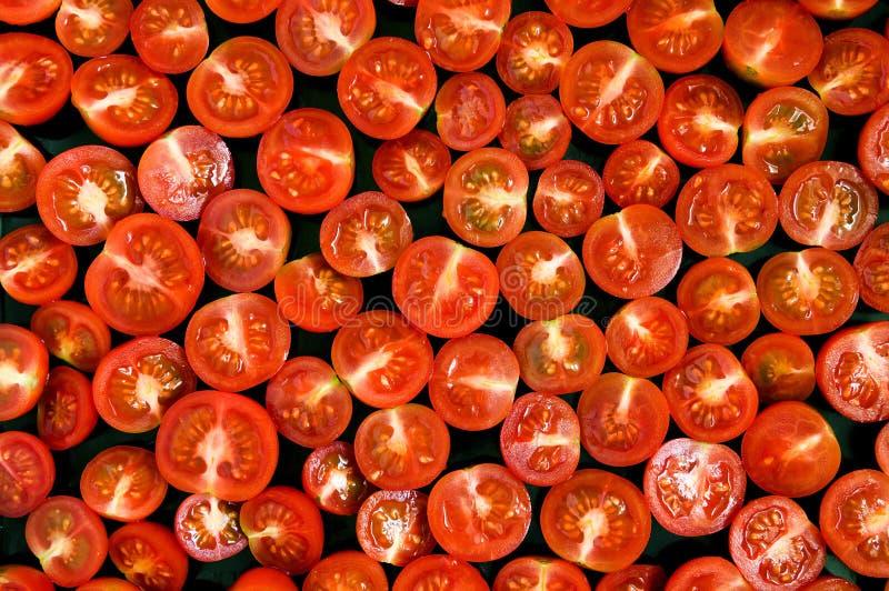 Κόκκινα μισά ντοματών στο μαύρο τηγάνι στοκ φωτογραφία με δικαίωμα ελεύθερης χρήσης