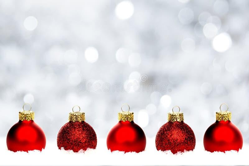 Κόκκινα μπιχλιμπίδια Χριστουγέννων στο χιόνι με το ασημένιο υπόβαθρο στοκ φωτογραφίες