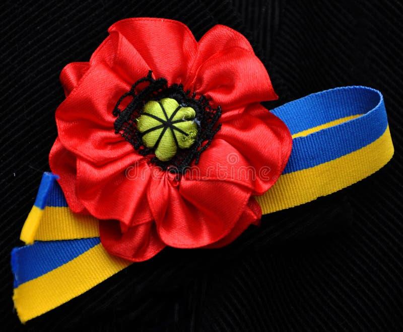 Κόκκινα λουλούδια παπαρουνών και ουκρανική σημαία κορδελλών στοκ εικόνα