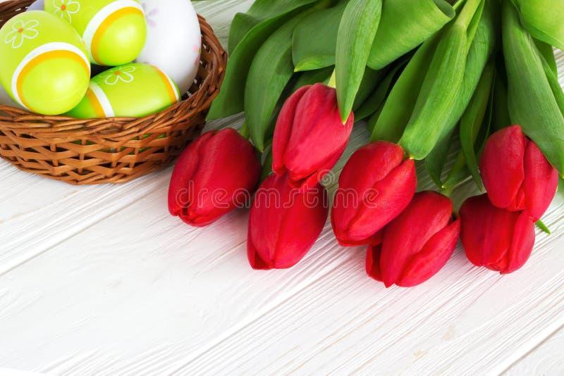 Κόκκινα λουλούδια τουλιπών ανθοδεσμών με τα αυγά Πάσχας στον παλαιό ξύλινο πίνακα στοκ φωτογραφία