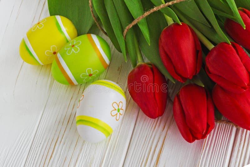 Κόκκινα λουλούδια τουλιπών ανθοδεσμών με τα αυγά Πάσχας στον παλαιό ξύλινο πίνακα στοκ εικόνα