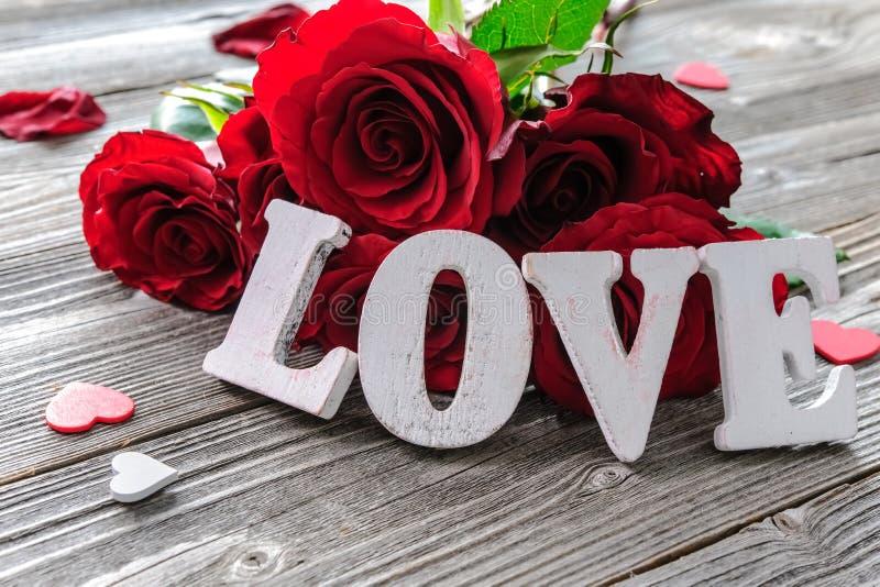 Κόκκινα λουλούδια τριαντάφυλλων και αγάπη λέξης στοκ εικόνα με δικαίωμα ελεύθερης χρήσης