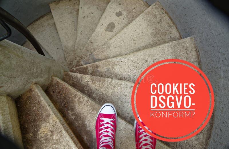 Κόκκινα πάνινα παπούτσια στη σπειροειδή σκάλα κατά να πάει προς τα κάτω με την επιγραφή στα γερμανικά μπισκότα DSGVO-DSGVO-konfor στοκ εικόνα