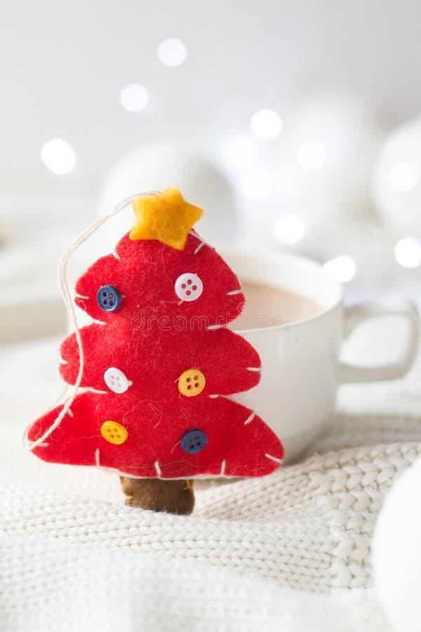 Κόκκινα παιχνίδι χριστουγεννιάτικων δέντρων και φλυτζάνι της καυτής σοκολάτας στοκ εικόνα