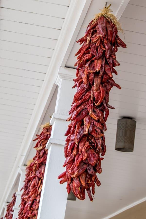 Κόκκινα πιπέρια τσίλι που κρεμούν υπαίθρια με τις άσπρες στήλες στοκ εικόνες