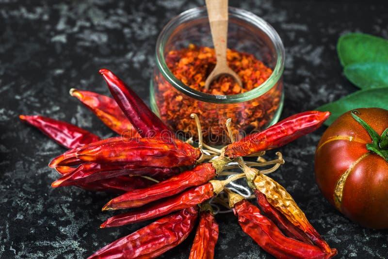 Κόκκινα πιπέρια τσίλι στη δέσμη και συντριμμένος στα τσίλι στοκ εικόνες