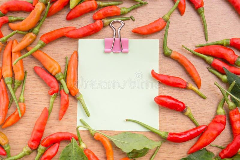 Κόκκινα πιπέρια τσίλι και έγγραφο σημειώσεων στοκ εικόνα