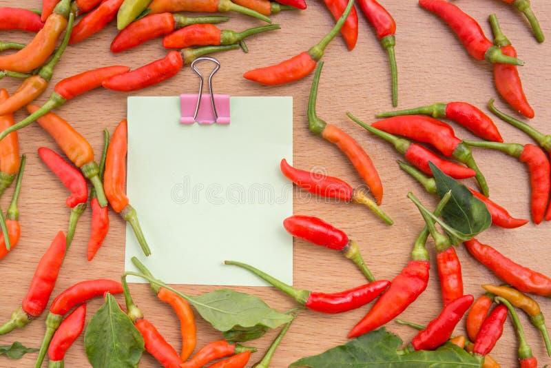 Κόκκινα πιπέρια τσίλι και έγγραφο σημειώσεων στοκ εικόνες