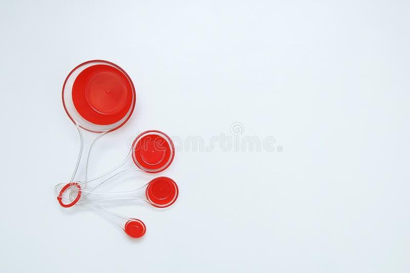 Κόκκινα πλαστικά μετρώντας κουτάλια για το μαγείρεμα Άσπρη ανασκόπηση στοκ εικόνες με δικαίωμα ελεύθερης χρήσης