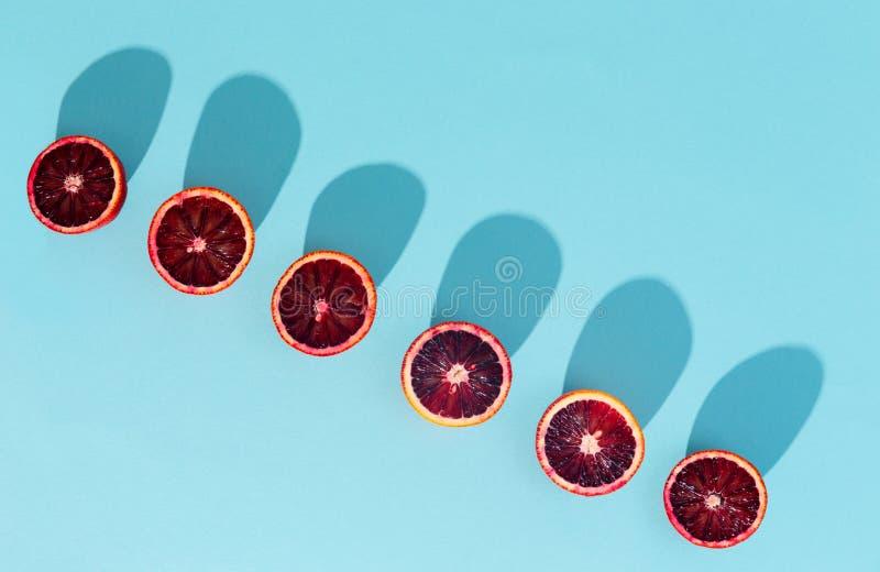 Κόκκινα πορτοκάλια στο τολμηρό μπλε υπόβαθρο Δημιουργικός μινιμαλισμός και στοκ φωτογραφία με δικαίωμα ελεύθερης χρήσης