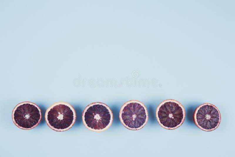 Κόκκινα πορτοκάλια στο τολμηρό μπλε υπόβαθρο Δημιουργικός μινιμαλισμός και στοκ εικόνες