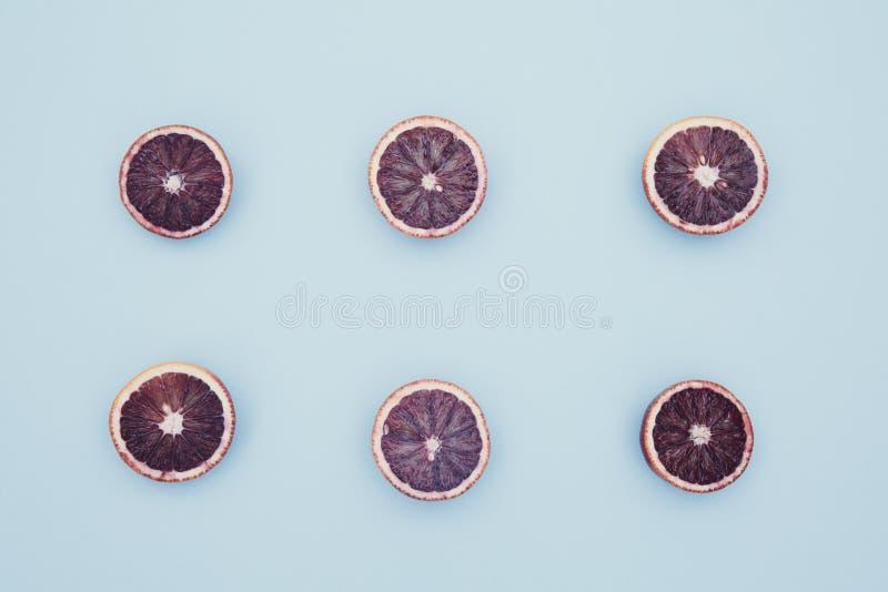 Κόκκινα πορτοκάλια στο τολμηρό μπλε υπόβαθρο Δημιουργικός μινιμαλισμός και στοκ φωτογραφίες με δικαίωμα ελεύθερης χρήσης