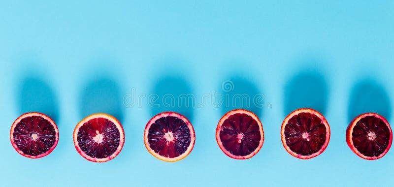 Κόκκινα πορτοκάλια στο τολμηρό μπλε υπόβαθρο Δημιουργικός μινιμαλισμός και στοκ φωτογραφία