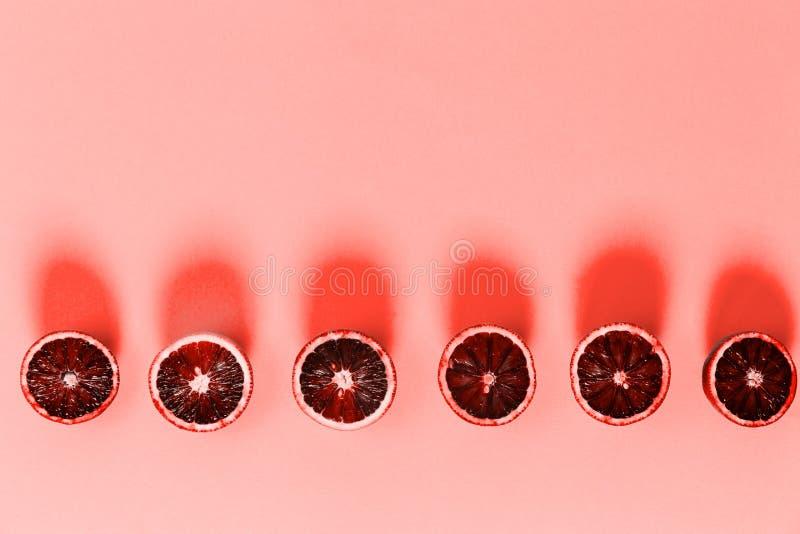 Κόκκινα πορτοκάλια στο τολμηρό μπλε υπόβαθρο Δημιουργικός μινιμαλισμός και σύγχρονη έννοια σχεδίων τροφίμων Θέμα κοραλλιών διαβίω στοκ εικόνες με δικαίωμα ελεύθερης χρήσης