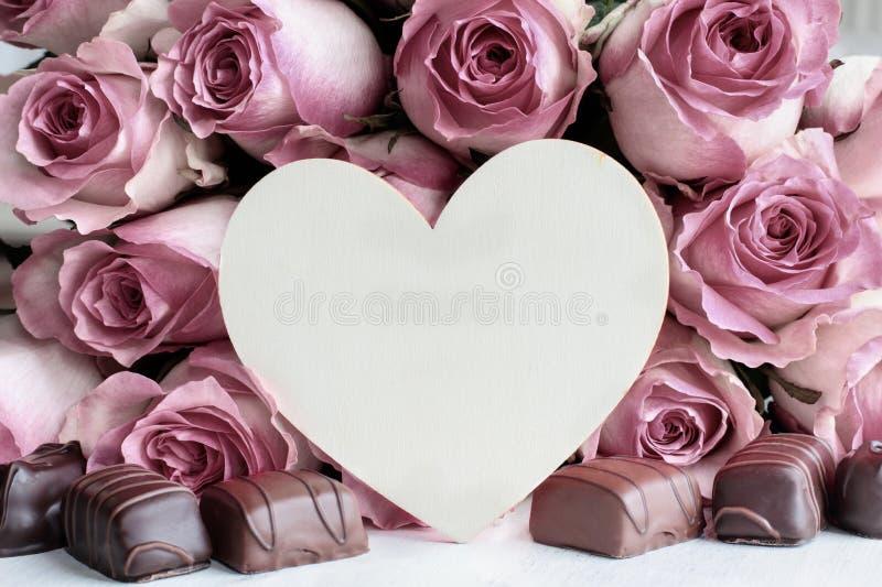 Κόκκινα ροζ λουλούδια Ξύλινη καρδιά και σοκολάτα Γλυκά στοκ φωτογραφίες