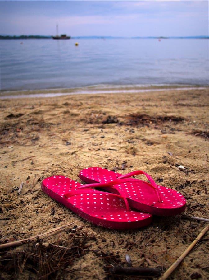 Κόκκινα σανδάλια στην παραλία στοκ εικόνες