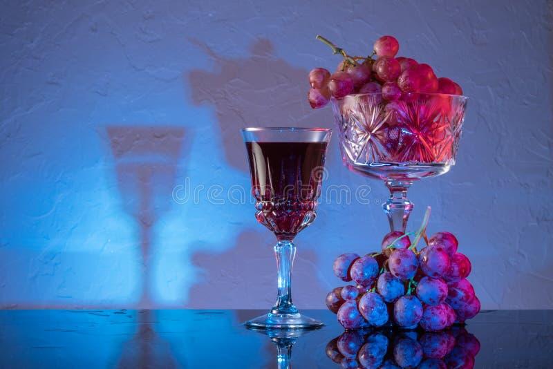 Κόκκινα σταφύλια και κόκκινο κρασί σε ποτήρι Ακόμη ζωή στοκ εικόνες