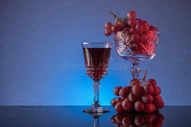 Κόκκινα σταφύλια και κόκκινο κρασί σε ποτήρι Ακόμη ζωή στοκ φωτογραφία με δικαίωμα ελεύθερης χρήσης