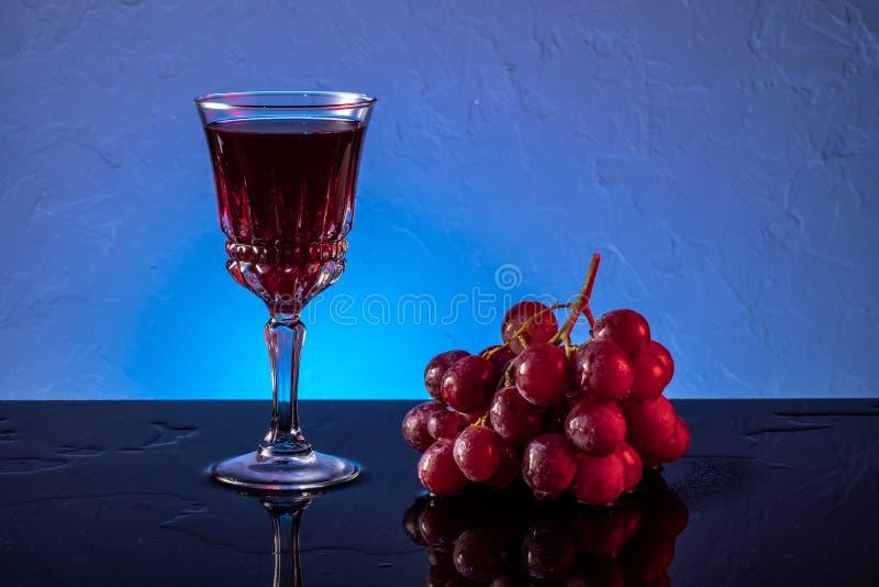 Κόκκινα σταφύλια και κόκκινο κρασί σε ποτήρι Ακόμη ζωή στοκ φωτογραφίες