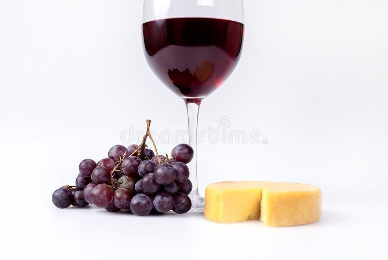 Κόκκινα σταφύλια και τυρί γκούντα με το κρασί στοκ εικόνες