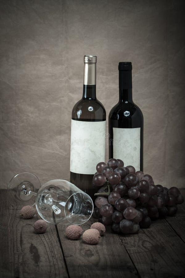 Κόκκινα σταφύλια με τα μπουκάλια κρασιού στοκ φωτογραφία