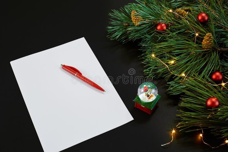 Κόκκινα σφαίρες και σημειωματάριο Χριστουγέννων που βρίσκονται κοντά στον πράσινο κομψό κλάδο στη μαύρη τοπ άποψη υποβάθρου Διάστ στοκ εικόνα