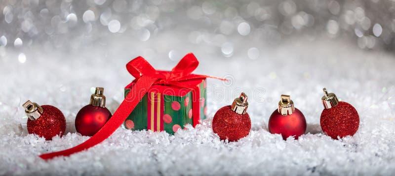 Κόκκινα σφαίρες Χριστουγέννων και κιβώτιο δώρων στο χιόνι, αφηρημένο υπόβαθρο φω'των bokeh στοκ φωτογραφία με δικαίωμα ελεύθερης χρήσης